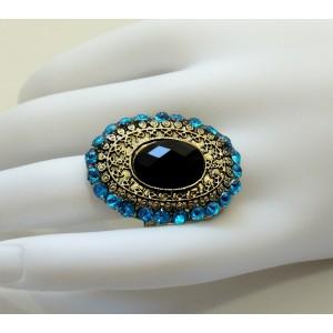 Grosse bague avec une pierre noire sur métal doré travaillé orné de strass bleus