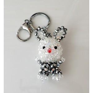 Bijou de sac en forme de lapin composé de perles facetées brillantes blanches et noires